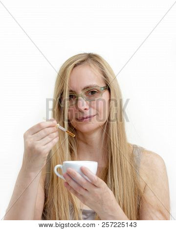 Middle aged fifty plus woman sitting on the bed and dripping drops in a cup of a pipette. Real portrait sick and frustrated woman during menopause. poster