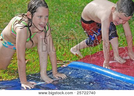 Young boy and girl racing during water play