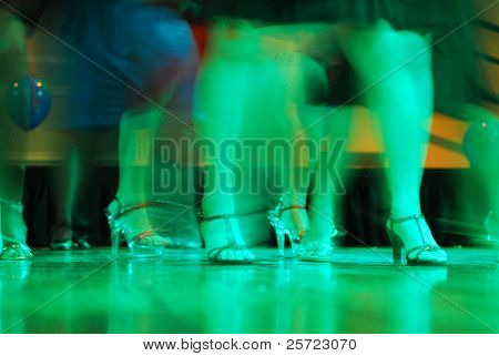 women in fancy high heeled shoes dancing during party, motion blur
