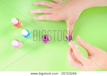 Young girl putting on own purple nail polish poster