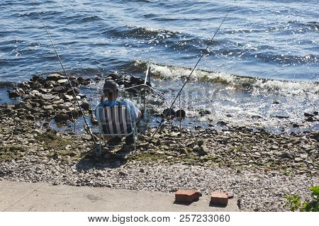 Fisherman With Fishing Rods Sits In A Deckchair Not The Shore Of The River Or The Sea. Recreation An
