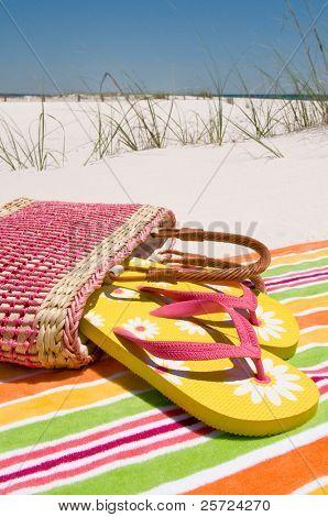 Beach sandals at seashore on towel