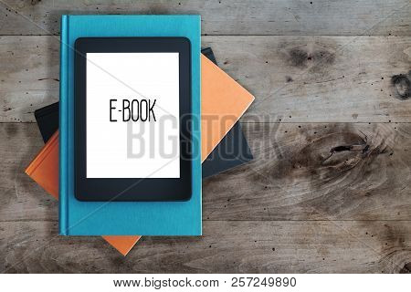 Top View Of E-book Reader On A Stack Of Books On Rustic Wooden Table Concept