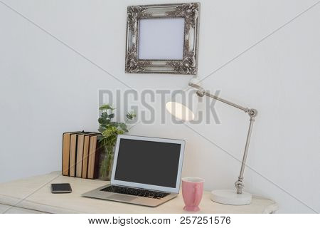Electronic gadgets, lamp, book, mug, flora and book on table against white wall
