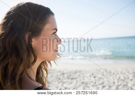 Thoughtful young woman looking away at beach on sunny day