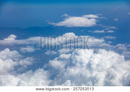 White fluffy clouds background hanging on blue sky over mountain. Aerial photo from airplane's window.
