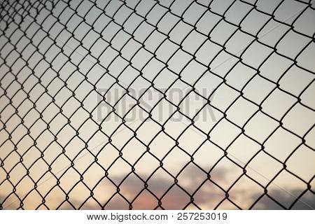 Sky through wire mesh fence. Blur background, close up view of link cage, wallpaper.