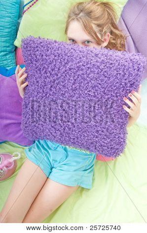 Teenager hiding behind pillow