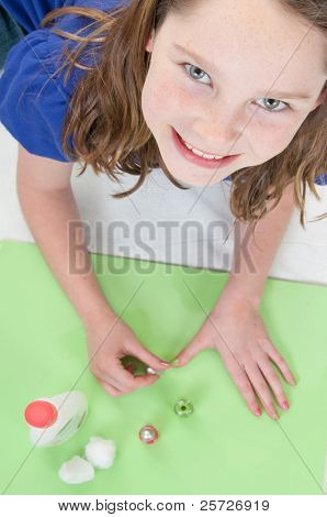 young girl happily polishing nails