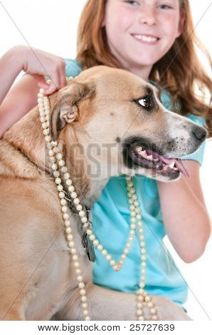 girl putting jewelry on dog