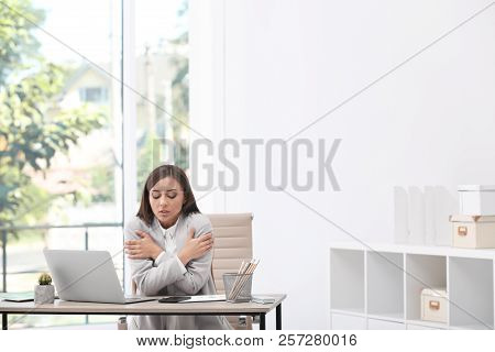 Young Woman Suffering From Cold In Office. Air Conditioner Malfunction