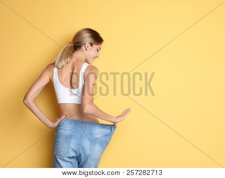Young Slim Woman In Old Big Jeans Showing Her Diet Results On Color Background