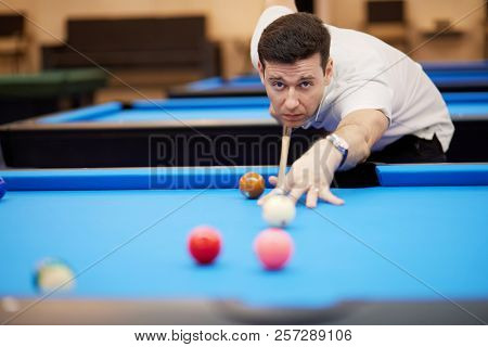 Man aims white ball with cue stick on pool table in club.