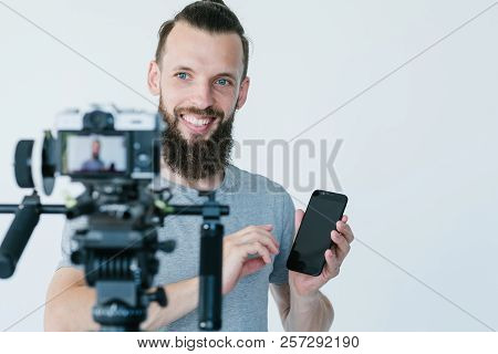 Social Media Influencer At Work. Blogger Shooting A Commercial Or Independent Review. Man Holding A