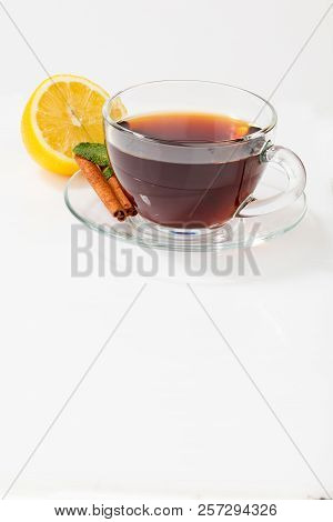 A glass cup with black tea on a saucer with mint, cinnamon, as well as lemon. poster
