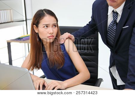 Angry Unhappy Asian Secretary Woman Looking Hand's Boss Touching Her Shoulder In Workplace. Sexual H