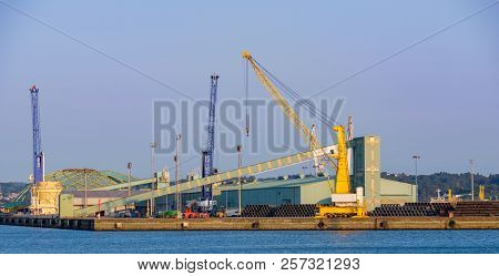 Industrial Port Facilities In Spain With Heavy Cranes And A Conveyor Belt