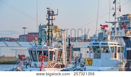 Exterior Of The Control Bridges Of Two White Tugboats With Metallic Red Water Hoses In The Port Of L
