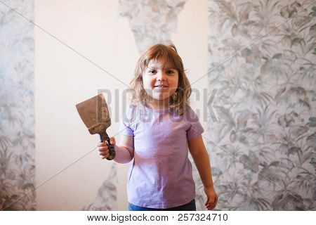 Adorable little girl repairing wall in apartment, holding putty knife old wall at the background. Empty place fot text, concept of easy home renovating. poster