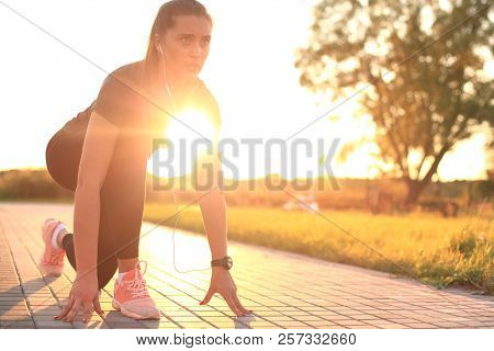 Young Fitness Attractive Sporty Girl Runner In Start Position Outdoor At Sunset Or Sunrise.
