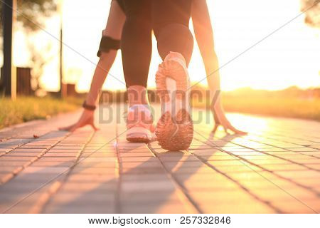 Young Fitness Attractive Sporty Girl Runner In Start Position, Closeup On Shoe, Outdoor At Sunset Or