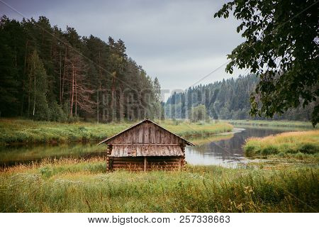 A Log Cabin On The River Bank Among The Pines, In Autumn