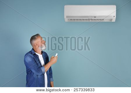 Mature Man Operating Air Conditioner On Color Background