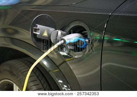 Electric Car Charging On Parking Lot With Electric Car Charging Station. Close Up Of Power Supply Pl