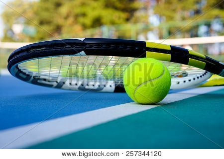 Close Up Tennis Ball And Rasket On White Court Line On Hard Modern Blue Court With Net Balls Trees I