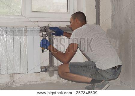 Plumber Installs The Radiator