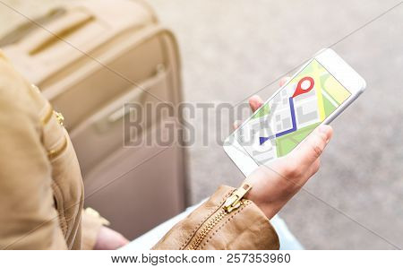 Tourist Using Map In Phone App To Navigate And Find Location Of Hotel In City. Woman With Smartphone