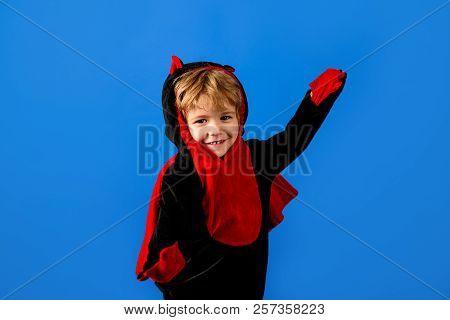 Little Kid In Dragon Costume. Kid Boy In Dragon Fancy Dress. Toddler Wearing Halloween Dinosaur Cost