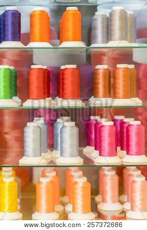 Background with a lot of colorful coils with threads. Bobbins are stacked in three rows, one on the other. The winding is erratic. Multicolored threads BANNER, vertical photo poster