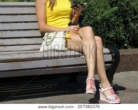 Slim Blonde Girl In A Short Yellow Dress And Sandals On A High Platform Sitting With A Smartphone In
