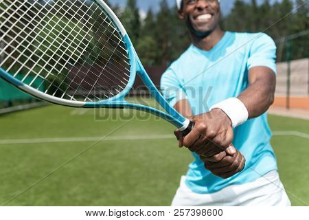 Smiling Man Is Going To Hit Ball During Tennis Match