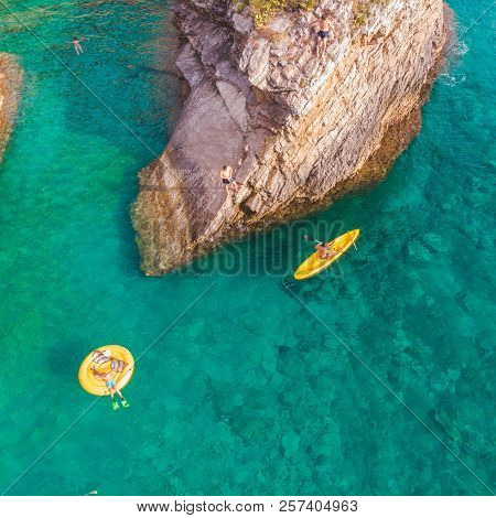 Man Swimming In Kayak Near Rocky Cliff. People To Jump From Cliff Into Sea Water