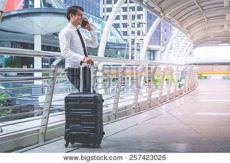 Business Tourist Traveler With Luggage Is Using His Mobile Phone