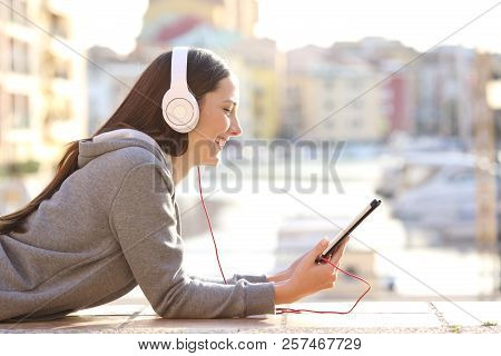 Side View Portrait Of A Happy Teen Watching Media Content In A Tablet Lying On The Sidewalk On Vacat