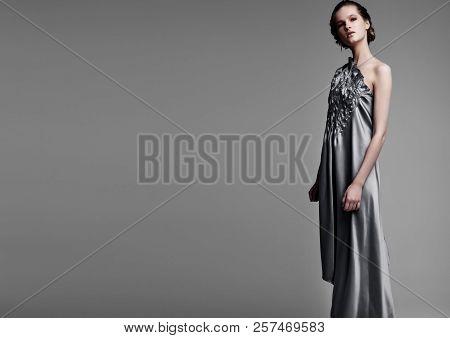 Beautiful Fashion Model Wearing High Couture Silk Dress On Grey Background