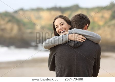Happy Couple Of Teens Hugging Meeting On The Beach