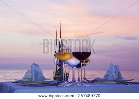 Silhouette Glass Of Wine And Equipment On A Wooden Table With Seascape And Skyline In The Evening Wi