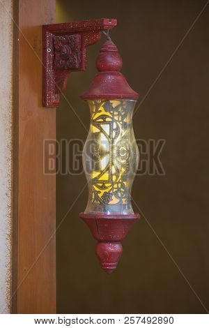 Classic Golden Lamp With Lights On Vibrant Burgundy Wall Background. Decorative Colorful Architectur
