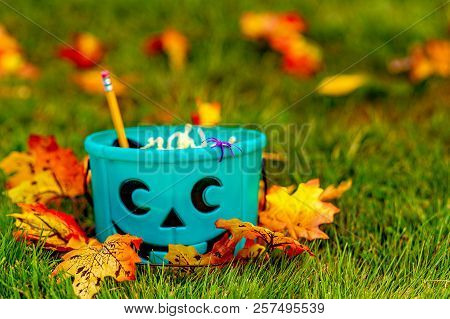 Teal Bucket With Non-food Treats Outside. Trick Or Treating. The Concept Of Health For Children In T