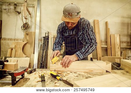 Experienced Carpenter In Work Clothes And Small Buiness Owner Working In Woodwork Workshop,  Using S
