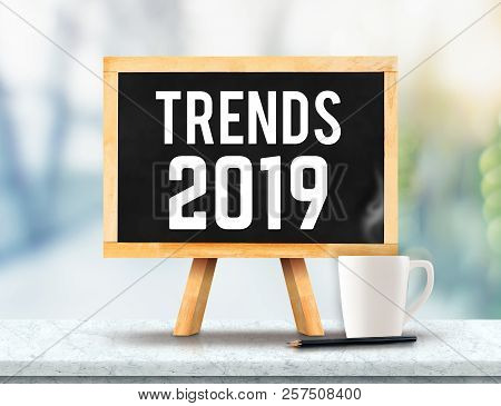 Trends 2019 On Blackboard With Easel On Marble Table With Sun And Blur Green Tree Bokeh Background.b