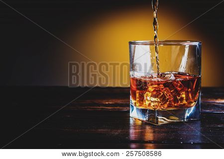 Alcohol Drink Whisky, Whiskey Or Bourbon With Ice Cubes On Dark Wood Table And Orange Background