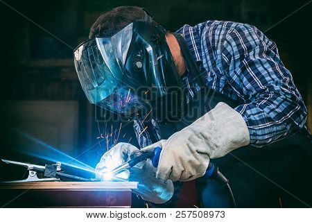 A Strong Man Welder In A Black T-shirt, In A Welding Mask And Welders Leathers Weld Metal Welding Ma