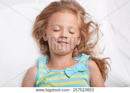 Healthy Appealing Little Girl With Long Messy Hair, Keeps Eyes Shut, Dressed In Pyjamass, Has Pleasa