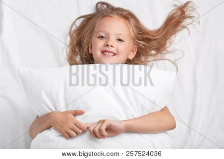 Satisfied Playful Girl With Charming Smile, Embraces Pillow, Lies On White Pillow, Has Good Rest, En