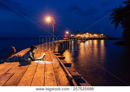 Woman reading book at dusk, using forehead light, on a wooden bridge, Hatta island, Maluku, Indonesia